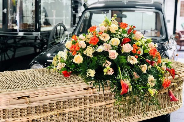 Wicker coffin with sunning floral tribute on top