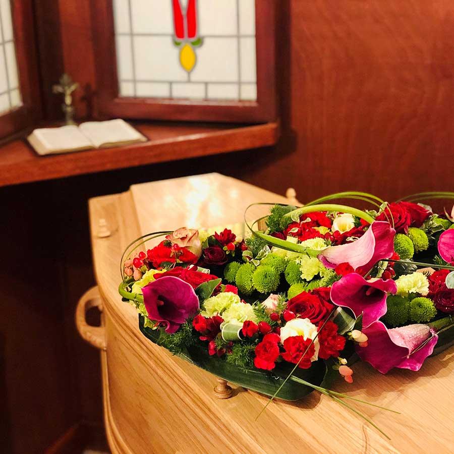 Coffin with flowers in the Hopkinson Wootton Lovatt Chapel of rest