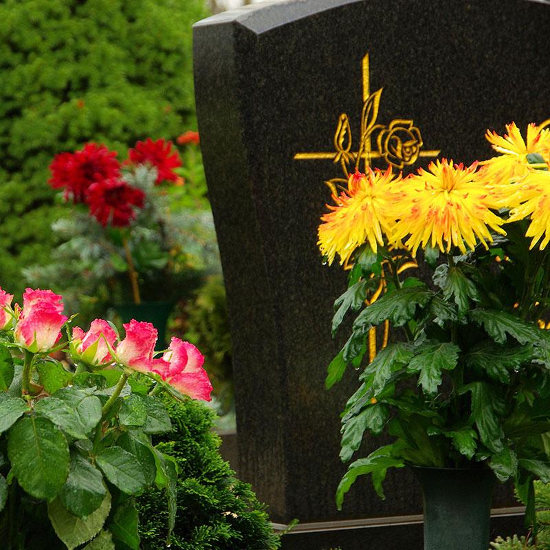 Black marble gravestone with engraved golden flower